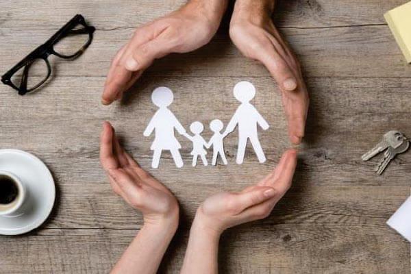 Mains entourant une famille en papier